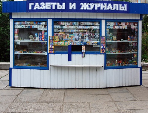 На фотографии изображен киоск, витрина которого заставлена различной полиграфической продукцией. Сверху – вывеска «Газеты и журналы».